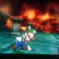 Luigi's Mansion Luigi glisse sur le sol marbré devant un mur de feu