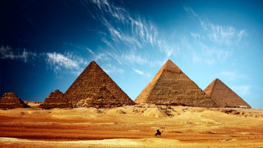Pyramides en Egypte avec gens sur un chameau au premier plan