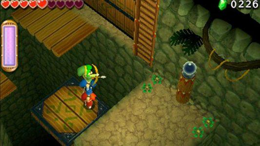 Triforce Heroes Les Link font un totem pour tirer une flèche sur une orbe