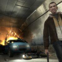 GTA IV Niko Bellic prend la pose devant des véhicules en feu