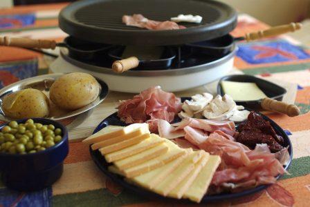 appareil à raclette avec fromage, charcuterie et pommes de terre