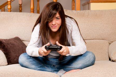 Jeune femme qui joue à la console sur un sofa